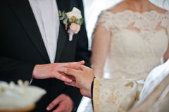 Priest puts wedding ring at grooms hand at church. Royalty Free Stock Image