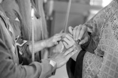 The priest puts the wedding rings on the fingers of the bride and groom in the church. Black and white photo. The priest puts the wedding rings on the fingers of stock photo