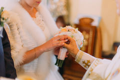 The priest is putting the golden wedding ring on the bride. Close-up view of the hands. The priest is putting the golden wedding ring on the bride. Close-up Royalty Free Stock Photography
