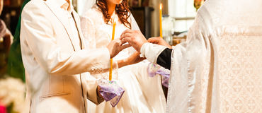 Priest is putting the ring on bride's finger during orthodox wedding ceremony Royalty Free Stock Photos