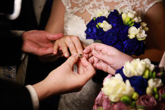 Priest putting a ring on bride's finger during wedding ceremony Stock Photos