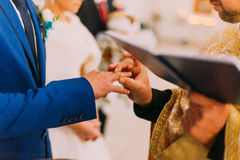 The priest putting a ring on groom's finger during traditional wedding in church.  Royalty Free Stock Photo