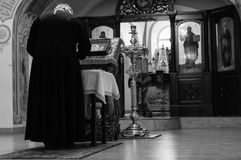 The priest reads the prayer. Black and white background Royalty Free Stock Photo