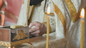The priest reciting the prayer from bible, two holy candles on foreground. Close-up. Male`s hand is touching the holy book on background. Focus changed. Two holy stock video footage
