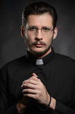 Priest with rosary beads. Portrait of priest standing isolated o. N black Stock Image