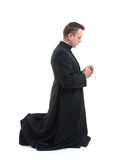 Priest with rosary. Catholic priest klneeling and saying his rosary beads royalty free stock photography
