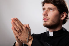 Priest with rosary. Priest praying in focus with a rosary Stock Image