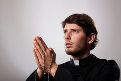Priest with rosary. Young priest is earnestly praying the rosary Stock Photo