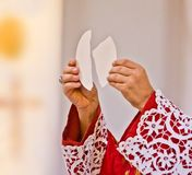 Hands of the priest raise the body of Christ royalty free stock images
