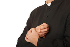 Priest's hands with rosary. Real cassock stock photo