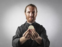 Priest with sacred host. Priest holding sacred host in his hands royalty free stock photo