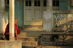 The monk sat facing the old building. royalty free stock photos