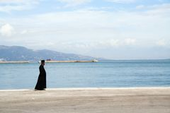 The priest and the sea. An Orthodox priest standing on the ferry dock on Corfu island, Greece royalty free stock photo
