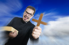 The priest showing cross and bible Royalty Free Stock Photography