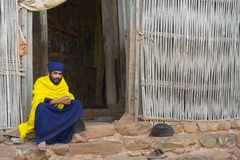 Priest sits at the entrance to the ancient church Ura Kidane Mehret in Bahir Dar, Ethiopia. Stock Photos