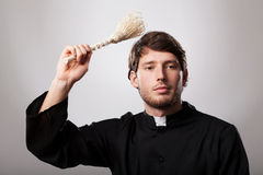 Priest with sprinkler Royalty Free Stock Photo