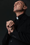Priest standing with eyes closed and praying. Over black background Royalty Free Stock Image