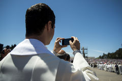 Priest taking a photograph with his mobile phone at the Sanctuary of Fatima during the celebrations of the apparition of the Virgi Stock Images