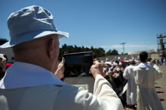 Priest taking a photograph with his mobile phone at the Sanctuary of Fatima during the celebrations of the apparition of the Virgi Royalty Free Stock Photos