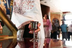 Priest taking wine in silver cup for wedding ceremony. Orthodox church Royalty Free Stock Photos