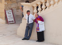 A priest is talking. This situation is photographed on the island of Gozo, just before a funeral Royalty Free Stock Image