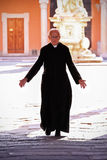 Priest walking on the churchyard in Pisa. Stock Photography