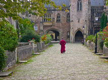 Priest walking through cloisters Wells. Priest walking towards Wells Cathedral through the housing cloisters used by the staff of the cathedral royalty free stock image