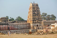 Priest walking infront of temple, Hampi Stock Photography