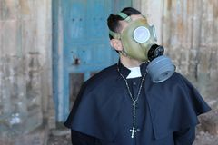 Priest wearing a gas mask.  stock image