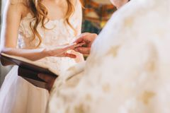 Priest wears a wedding ring on bride finger. The exchange of rings during an Orthodox wedding, the priest wears the ring bride and groom, wedding day, the church Royalty Free Stock Images