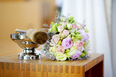 Priest during a wedding ceremony/nuptial mass. Bridal bouquet in a chruch during wedding ceremony Stock Photography