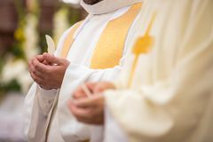 Priest` hands during a wedding ceremony/nuptial mass. Priest during a wedding ceremony/nuptial mass shallow DOF; color toned image stock images