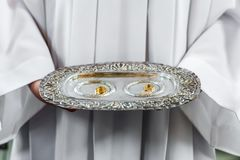 Priest and wedding rings on silver platter stock images