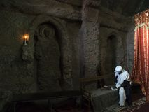 Priest with white clothes sits in rock church stock images
