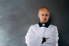 Priest in white surplice and black shirt with cleric collar. Catholic priest in white surplice and black shirt with cleric collar with crossed hands royalty free stock images