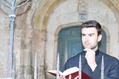 Priester, der ein Rosenbeet beim Ablesen der Bibel mit Kopienraum küsst stockbild