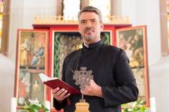 Priester in der Kirche mit Bibel vor Altar Stockbilder