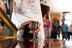 Priester, der Wein in der silbernen Schale für Hochzeitszeremonie nimmt lizenzfreie stockfotos