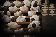 Priester, die in der Kirche sitzen Stockfotografie