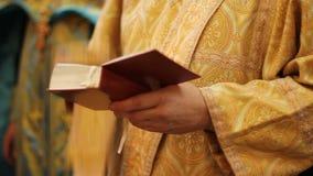 Priester die met goddelijke liturgie beginnen, kruisen en god voor zegen bidden stock footage