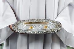 Priester en trouwringen op zilveren schotel stock afbeeldingen