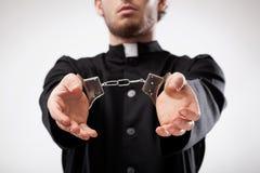 Priester mit Handschellen gefesselt Lizenzfreie Stockfotos