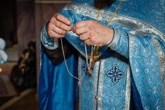Priester trägt das gewidmete Kreuz während der Kind-` s Taufe stockfotografie