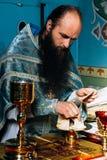 Priester widmet Brot lizenzfreie stockfotografie