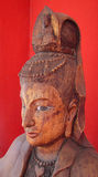 Priestess Bust Carved in Thai Wood. With ornate headgear and beaded crown. Glancing to the side against a red background Royalty Free Stock Images