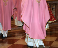 Priests with cassock in church during the Holy Mass. Many priests with pink cassock in church during the celebration of Holy Mass royalty free stock images