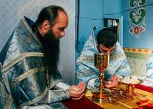 Priests consecrates bread Stock Image