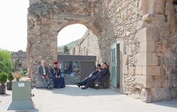 Priests of the Georgian Orthodox Church. MTSKHETA, GEORGIA- AUGUST 17, 2013: Priests sit and talk in the shadow of a stone wall royalty free stock photos