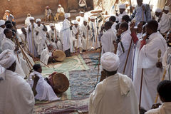 Priests, Lalibela. Priests in a monolithic church, one priest is talking into a microphone and two others are sat down with drums stock image
