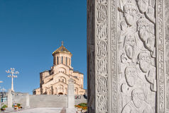 Priests and monks on relief of stone column near the Holy Trinity Cathedral in Tbilisi stock images